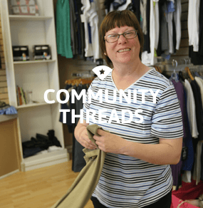 Woman folding clothes at Community Threads