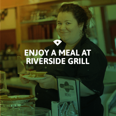 Woman serving pie at Riverside Grill colored green
