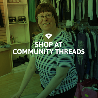 Woman folding clothes at Community Threads colored green